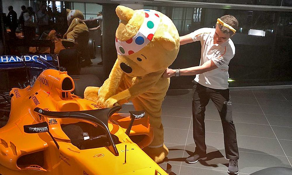 McLaren driver Lando Norris helps BBC Children In Needs's Pudsey the Bear into the cockpit of the MCL33.