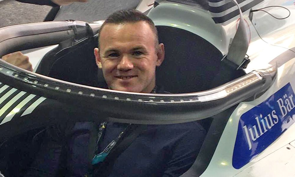 Wayne Rooney tries out the seat of José María López's Geox Dragon Penske car.
