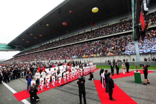 The grid observes the national anthem. 14.04.2019. Formula 1 World Championship, Rd 3, Chinese Grand Prix, Shanghai, China, Race Day.  - www.xpbimages.com, EMail: requests@xpbimages.com - copy of publication required for printed pictures. Every used picture is fee-liable. © Copyright: Bearne / XPB Images