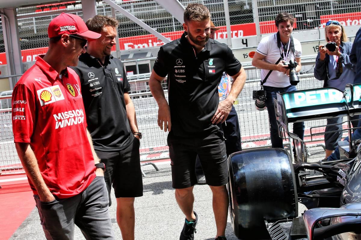 Sebastian Vettel (GER) Ferrari with members of the Mercedes AMG F1 team.
