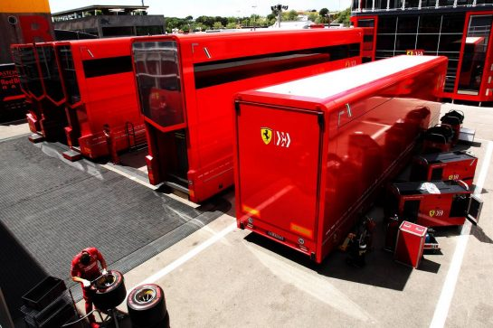 Ferrari mechanic working behind trucks in the paddock.