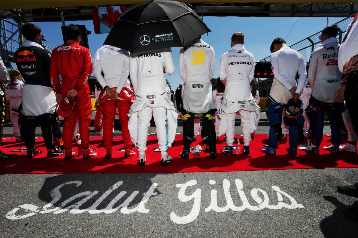 Drivers as the grid observes the national anthem.