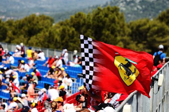 Ferrari flag with fans in the grandstand.