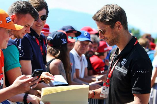 Romain Grosjean (FRA) Haas F1 Team signs autographs for the fans.