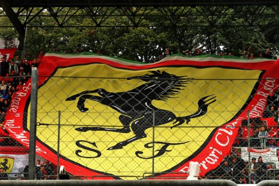 Circuit atmosphere - large Ferrari flag with fans in the grandstand.