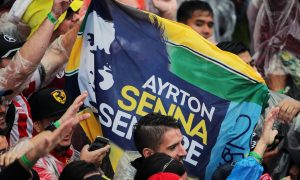 An Ayrton Senna banner with fans at the podium.