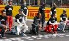 Drivers on the grid take a knee before the start of the race.