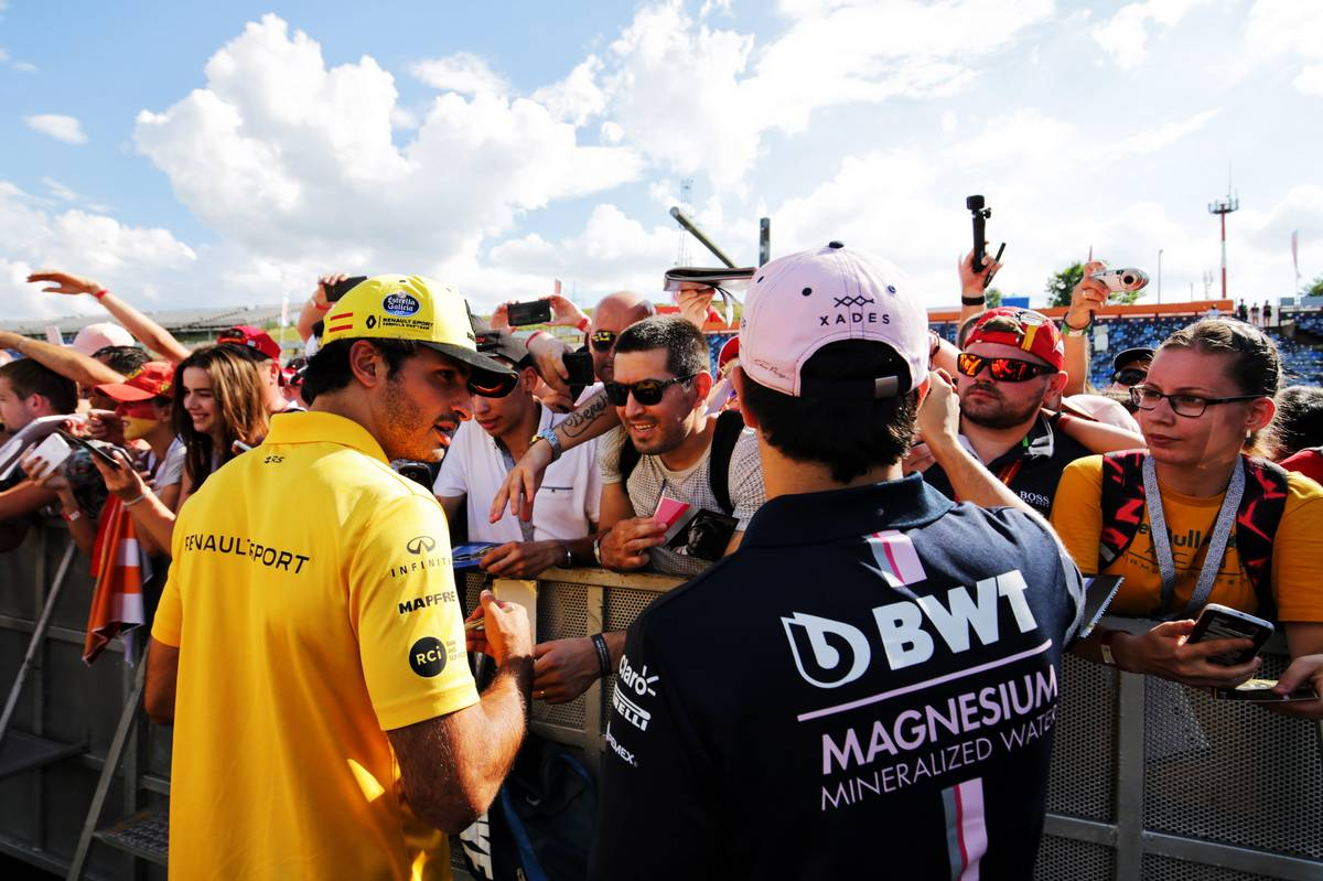 Carlos Sainz Jr (ESP) Renault Sport F1 Team and Sergio Perez (MEX) Sahara Force India F1 sign autographs for the fans. 26.07.2018